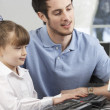 Teacher helping girl using computer in class — Stock Photo #11889469