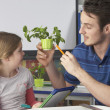 Stock Photo: Girl learning about plants with teacher