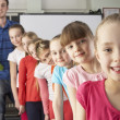 Teacher with line up of children in class — Stock Photo