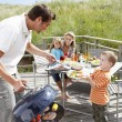 Stock Photo: Family on vacation having barbecue