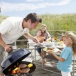 Family on vacation having barbecue - Stok fotoğraf
