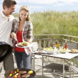 Couple on vacation having barbecue — Stock Photo