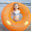 Child on beach with giant rubber ring — Stock Photo