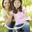 Girl on bike with mother — Stock Photo