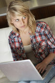 Guilty Looking Teenage Girl Using Laptop At Home — Stock Photo
