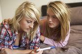 Twee tienermeisjes liggend op bed kijken naar zwangerschap testing kit — Stockfoto