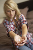 Depressed Teenage Girl Sitting In Bedroom With Pills — Stock Photo