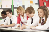 Teenage Students Studying In Classroom With Teacher — Stockfoto