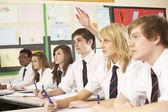 10 代の学生を教室で勉強して質問に答える — ストック写真