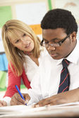 Genç öğrenci sınıfta öğretmeni ile çalışma — Stok fotoğraf
