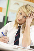 Stressed Female Teenage Student Studying In Classroom — Stock Photo