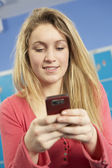 Female Teenage Student Using Mobile Phone By Lockers In School — Stock Photo