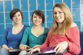 Female Teenage Students Relaxing By Lockers In School — Stock Photo