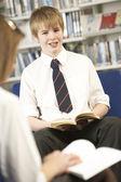 Estudiante adolescente masculino en biblioteca de lectura — Foto de Stock