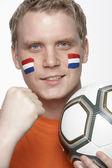 顔に描かれたオランダの国旗を持つ若い男性フットボールのファン — ストック写真