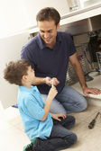 Son Helping Father To Mend Sink In Kitchen — Stock Photo