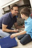 Hijo ayudando a papá para reparar fregadero de cocina — Foto de Stock