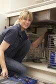 Fontanero mujer trabajando en fregadero de cocina — Foto de Stock