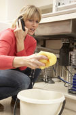 Woman Mopping Up Leaking Sink On Phone To Plumber — Photo