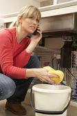 Femme de nettoyage évier qui fuit sur le téléphone pour plombier — Photo