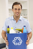 Hombre que sostiene la papelera de reciclaje en casa — Foto de Stock