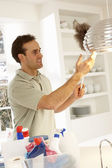 Man Cleaning Light Fitting With Feather Duster — Stock Photo