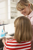 Mother And Daughter Washing Hands At Kitchen Sink — Stock Photo