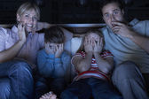 Family Watching Scary Programme On TV Sitting On Sofa Together — Stock Photo