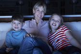 Madre y niños viendo el programa en tv sentados en subvención tog sofá — Foto de Stock
