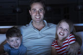 Father And Children Watching Programme On TV Sitting On Sofa Tog — Stock Photo