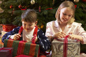 Children Opening Christmas Present In Front Of Tree — Stock Photo
