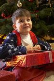 Joven apertura regalo delante de árbol de navidad — Foto de Stock