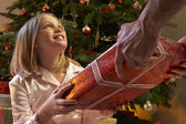 Young Girl Receiving Christmas Present In Front Of Tree — Стоковое фото