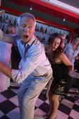 Senior Man Dancing With Younger Woman In Busy Bar — Stock Photo
