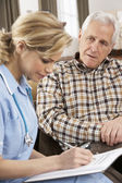 Senior Man Talking To Health Visitor At Home — Stock Photo
