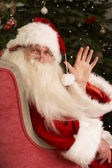 Santa Claus Sitting In Armchair In Front Of Christmas Tree — Stock Photo
