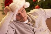 Yorgun adam noel ağacı rahatlatıcı — Stok fotoğraf