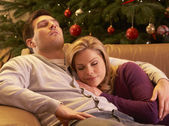 Tired Couple Relaxing In Front Of Christmas Tree — Stock Photo