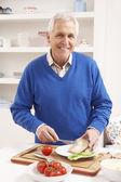 Senior Man Making Sandwich In Kitchen — Stock Photo