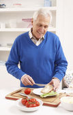Senior Man Making Sandwich In Kitchen — Stok fotoğraf