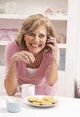 Haute femme appréciant une boisson chaude tandis que sur le téléphone — Photo