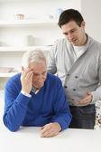 Crecido hijo consolando a padres senior — Foto de Stock