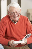 Senior Man Relaxing In Chair At Home Reading Book — Stock Photo