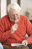 Senior man ontspannen in stoel thuis voltooiing kruiswoordraadsel — Stockfoto