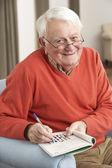 シニア男性自宅の椅子でリラックスしたクロスワード パズルを完了します。 — ストック写真