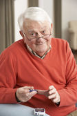 Senior Man Checking Blood Sugar Level At Home — Stok fotoğraf