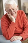 Senior Man Looking Sad In Chair At Home — Stock Photo