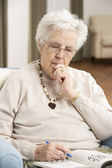 Senior Woman Relaxing In Chair At Home Completing Crossword — Stock Photo