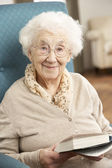 Senior Woman Relaxing In Chair At Home Reading Book — Stock Photo