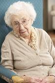 Haute femme regardant triste en fauteuil à la maison — Photo